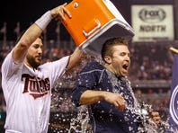 Jul 10, 2015; Minneapolis, MN, USA; Minnesota Twins third baseman Trevor Plouffe (24) dumps water on second baseman Brian Dozier (2) after Dozier hit a three run home run to win the game against the Detroit Tigers in the ninth inning at Target Field. The Twins win 8-6. Mandatory Credit: Bruce Kluckhohn-USA TODAY Sports