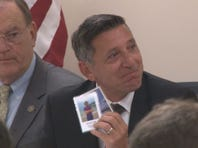 Director of National Drug Control Policy,  Michael Botticelli holds up cards of victims of opioid overdose.