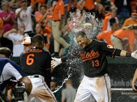 Aug 14, 2015; Baltimore, MD, USA; Baltimore Orioles second baseman Jonathan Schoop (6) sprays third baseman Manny Machado (13) with water after his two run walk off home run in the thirteenth inning against the Oakland Athletics at Oriole Park at Camden Yards. Baltimore Orioles defeated Oakland Athletics 8-6 in the thirteenth inning. Mandatory Credit: Tommy Gilligan-USA TODAY Sports