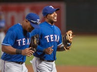 Texas Rangers third baseman Adrian Beltre (left) and shortstop Elvis Andrus (right) jog off the field