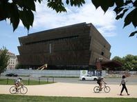 Tourists walk past the Smithsonian Museum of African American History and Culture that is currently under construction July 16, 2015 in Washington, DC. The museum is located on the National Mall near the Washington Monument and is scheduled to be completed and dedicated in 2016.