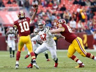 Washington Redskins quarterback Robert Griffin III (10) throws as Tampa Bay Buccaneers defensive end Larry English (57) chases in the fourth quarter at FedEx Field. The Buccaneers won 27-7 in 2014.