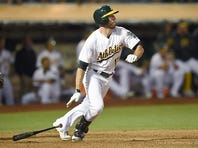 Ike Davis #17 of the Oakland Athletics hits an rbi single scoring Stephen Vogt #21 in the bottom of the ninth inning at O.co Coliseum on August 6, 2015 in Oakland, California.