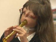 Juliana playing a recorder.