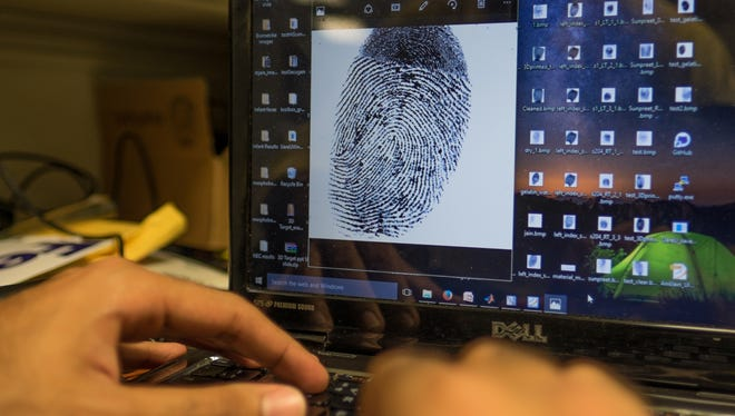 Doctoral student Sunpreet Arora analyzes a fingerprint while working on a project to unlock a homicide victimÕs smartphone.
