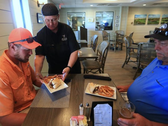 Gail Huesmann, executive chef at Black Marlin Bar and Grill in Port Aransas, delivers a tripleta sandwich to Leon Laskowski (left) and Philip Laskowski on Tuesday, April 4, 2016, at the restaurant. The father and son had never been at the restaurant and Leon Laskowski said he never would have ordered the sandwich but was amazed at the flavors.