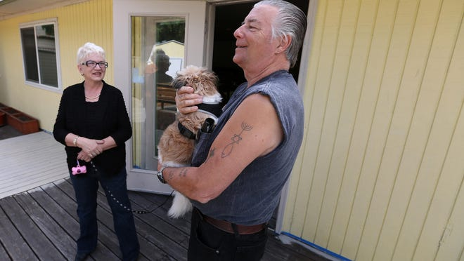 Matt Price, commander of American Legion Post 136, holds, Bella, a rescue dog who belongs to Élan Lambert, left, programs director for WestCare Oregon, on Thursday, July 16, at a Salem facility that will be long-term transitional housing for homeless veterans.