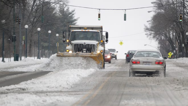 A snow plow clears Clifton Avenue in 2014.