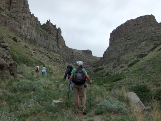 Hikers make their way up Square Butte during a National