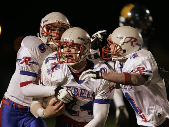 FILE – Jason Werner, middle, and Roncalli teammates Brandon Axum, left, and Chad Peterman, celebrate Werner's first interception of the evening. Roncalli beat Mooresville 20-16 in playoff action.