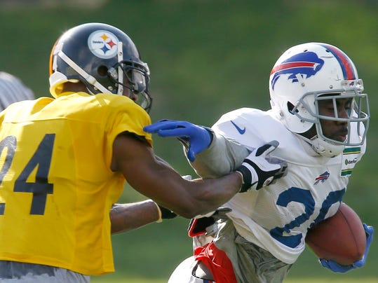 Buffalo Bills running back C.J. Spiller (28), runs away from Pittsburgh Steelers cornerback Ike Taylor (24) during a combined NFL football training camp session in Latrobe, Pa. on Wednesday, Aug. 13, 2014 . (AP Photo/Keith Srakocic)
