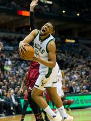 Jabari Parker grimaces as he drives to the basket against Miami's Luke Babbitt. Parker tore his ACL on the play Wednesday night at the BMO Harris Bradley Center.