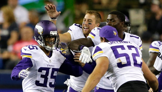 Minnesota Vikings cornerback Marcus Sherels, left, is greeted by teammates, including outside linebacker Chad Greenway (52). after Sherels intercepted a pass from Seattle Seahawks quarterback Trevone Boykin to score the go-ahead touchdown in a preseason NFL football game, Thursday, Aug. 18, 2016, in Seattle. The Vikings won 18-11. (AP Photo/John Froschauer)
