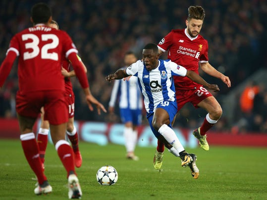 Porto's Majeed Waris vies for the ball with Liverpool's Adam Lallana, right, during the Champions League round of 16, second leg, soccer match between Liverpool and FC Porto at Anfield Stadium, Liverpool, England, Tuesday March 6, 2018. (AP Photo/Dave Thompson)