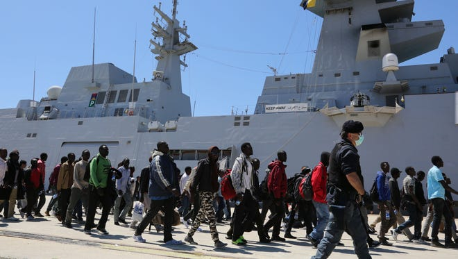 Rescued migrants disembark from an Italian Navy vessel in the harbor of Augusta, Sicily, Southern Italy, Wednesday, April 22, 2015. Italy pressed the European Union on Wednesday to devise concrete, robust steps to stop the deadly tide of migrants on smugglers' boats in the Mediterranean, including setting up refugee camps in countries bordering Libya. Italian Defense Minister Roberta Pinotti also said human traffickers must be targeted with military intervention. (AP Photo/Francesco Malavolta)