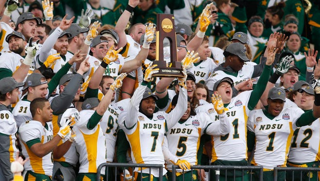 North Dakota State Bison defensive back Zach Colvin holds up a trophy after the Bison won their fourth consecutive FCS championship.