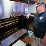 Owner Marc Shumate checks on the meats cooking slowly in the smoker Friday, March 20, 2015, at South Street Smokehouse, 3305 South St., No. 6, in Lafayette.