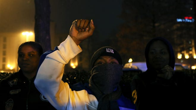 December 20, 2017 - Kevin Carson, 26, rises his fist as crews remove the Confederate statue of Jefferson Davis from Memphis Park on Wednesday night.