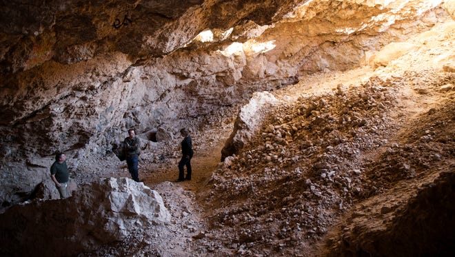 In this Tuesday, Dec. 19, 2017 photo, archaeologist Justin DeMaio, center, stands during a tour of the Gypsum Cave east of Las Vegas. A well-preserved horse skull collected more than 86 years ago from the cave near Las Vegas is helping scientists identify a new type of extinct, stilt-legged horse that died out during the last ice age. A team of researchers led by famed archaeologist Mark Harrington discovered the bone in the 1930s inside the Gypsum Cave.  (Erik Verduzco/Las Vegas Review-Journal via AP)