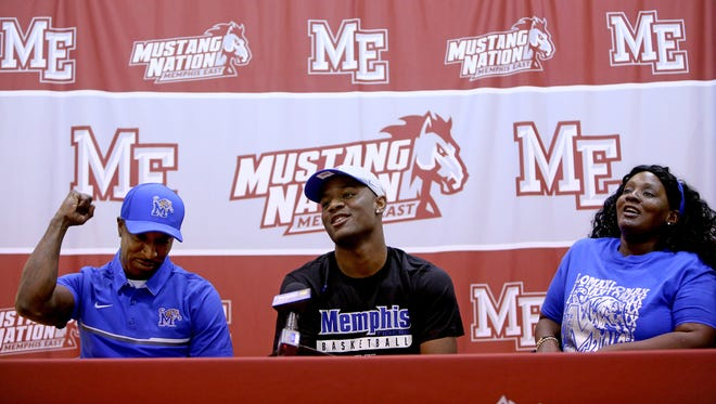 April 11, 2018 - East High School point guard Alex Lomax, flanked by his parents Alex Lomax, left, and Kamesha Jefferson, prepares to sign his national letter of intent to attend University of Memphis during an event at Lester Community Center on Wednesday.