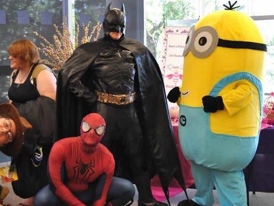 Batman, Spider-Man and a Minion converse at a previous