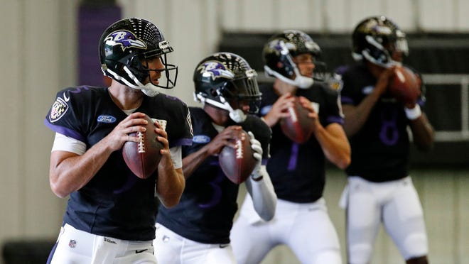 FILE - In this July 24, 2018, file photo, Baltimore Ravens quarterback Joe Flacco, left, runs a drill in front of quarterbacks Robert Griffin III, second from left, Josh Woodrum and Lamar Jackson during an NFL football training camp practice in Owings Mills, Md. Flacco has returned to the practice field for the first time since injuring his right hip on Nov. 4. Having finally received medical clearance to play, Flacco threw passes and worked on handoffs with fellow quarterbacks Lamar Jackson and Robert Griffin III during an indoor practice Thursday, Nov. 29, 2018. (AP Photo/Patrick Semansky, File)