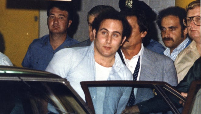 """Police officials surround David Berkowitz, 24, of Yonkers outside Brooklyn's 84th Precinct after his arrest as the """"Son of Sam"""" killer early Thursday, Aug. 11, 1977."""
