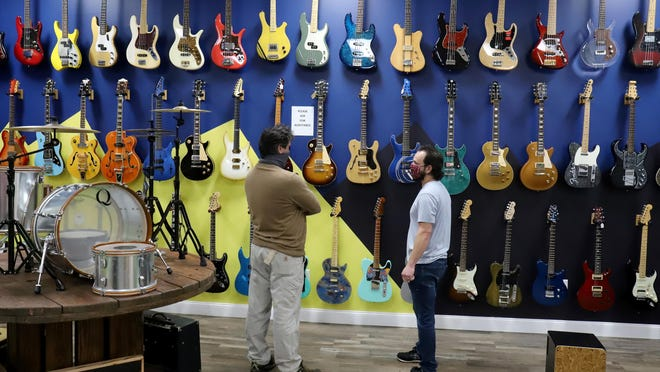 Ben Jones, left, talks with Vintage Vibes Manager James Henry on Nov. 17 about the music center's collection of vintage and boutique guitars. Vintage Vibes, 8819 Rogers Ave., is open 10 a.m. to 6 p.m. Monday through Saturday. The store has more than 400 guitars on display, ranging from beginner guitars to classic Gibson and Martin guitars. The collection also includes autographed guitars by Eric Clapton, Eddie Van Halen, Joe Bonamossa and more.