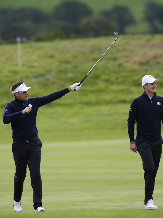 Europe's Ian Poulter waves to the crowd as he walks along the 3rd fairway with Justin Rose during a practice round ahead of the Ryder Cup golf tournament at Gleneagles, Scotland, Thursday, Sept. 25, 2014. (AP Photo/Peter Morrison)