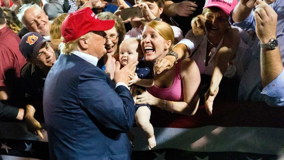 A woman with her baby shows excitement when Donald