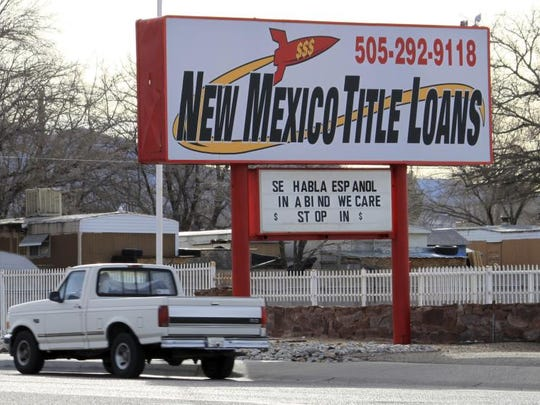 A truck heads east along historic Route 66, past one of the roughly 700 small lenders operating in New Mexico, in Albuquerque, N.M., on Friday, Feb. 3, 2017. Two New Mexico lawmakers have introduced legislation once again targeting the payday and title loan industry, seeking to cap interest rates at 36 percent.
