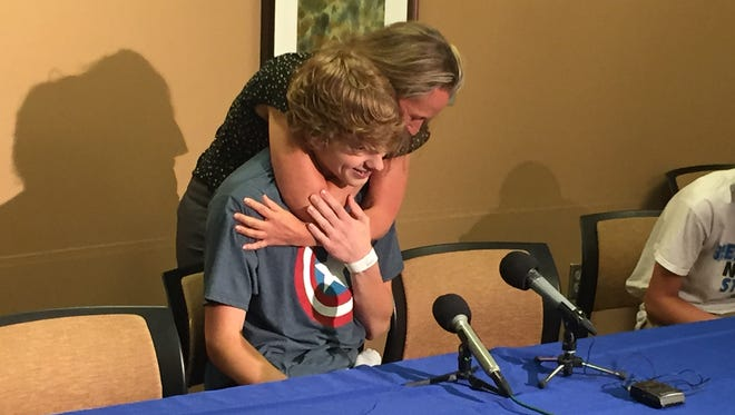 Danny Fleigle gets a hug from Sheila Merriman, a friend's mom, on Monday, June 27, at Hennepin County Medical Center.