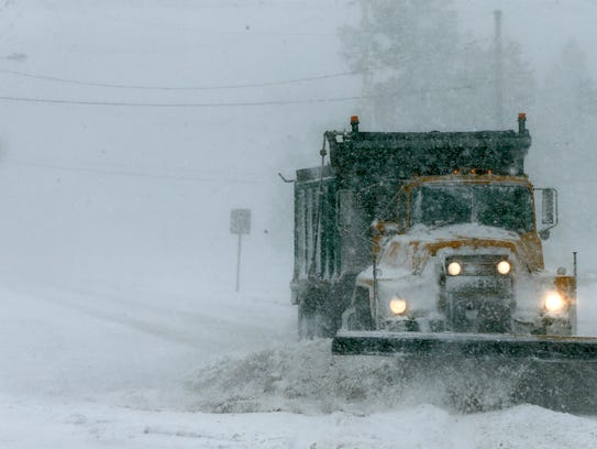 A snow plow works along Airport Road in Lakewood Thursday
