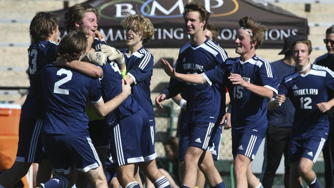 Maclay soccer players celebrate their Class 1A state title Thursday in DeLand.