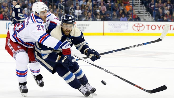 New York Rangers' Ryan McDonagh, left, tries to knock the puck away from Columbus Blue Jackets' Nick Foligno during the second period of an NHL hockey game Friday, Nov. 18, 2016, in Columbus, Ohio.