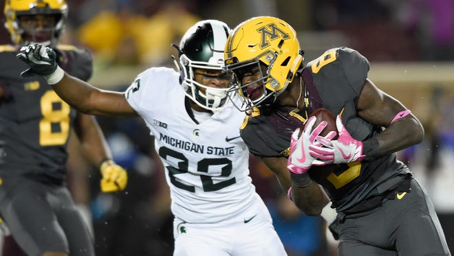 Tyler Johnson #6 of the Minnesota Golden Gophers carries the ball for a touchdown against Josiah Scott #22 of the Michigan State Spartans during the fourth quarter of the game on October 14, 2017 at TCF Bank Stadium in Minneapolis, Minnesota. The Spartans defeated the Gophers 30-27.