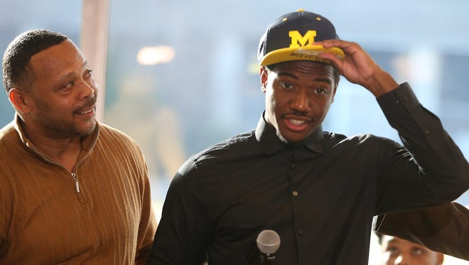 Detroit King cornerback Lavert Hill puts on a Michigan hat after selecting the Wolverines alongside Cass Tech head coach Thomas Wilcher on February 3, 2016, at the Horatio Williams Foundation headquarters in Detroit.