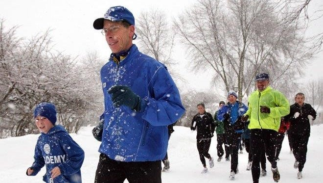 John Chandler, center, runs through a snowy day with his son,  Jack, and other runners.