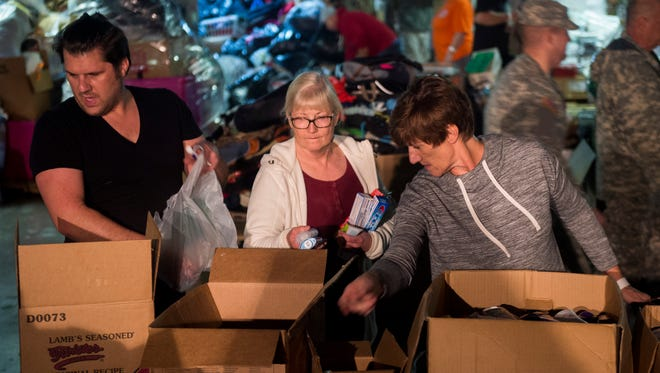 Volunteers sort through donated items at a donations warehouse in Sevierville on Monday, Dec. 5, 2016. Volunteer East Tennessee is currently in need of more than 1,800 volunteers over the next three days.