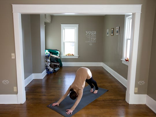Wellness Barn owner Tarah Mancl demonstrates the downward dog yoga pose in her studio in Wisconsin Rapids, Monday, Jan. 11, 2015.