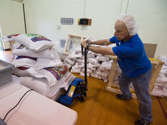 JD Dennis of Harrington pushes a pallet of lentils which will be in the 100,000 meals they are preparing and shipping to countries around the world during their day long packaging session at Calvary Wesleyan Church in Harrington.