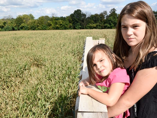 Kalia Espenlaub, right,  boosts her little sister, Alana, so she can look out over the corn maze from a bridge at Country Creek Produce Farm, 3746 Etter Road, Chambersburg.