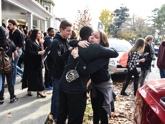 Students embrace at the end of a march against hate