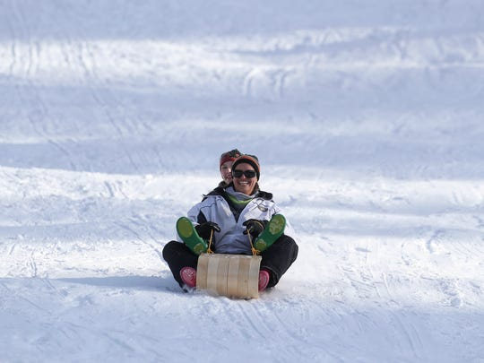Geannine Klein, front, rides a sled with her daughter Sierra at Snowman's Hill in Mt. Shasta.