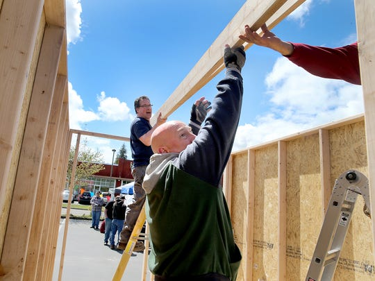 Volunteer Jim DeMott (center), from First Lutheran Community Church, steadies a roofing beam to a tiny cottage.