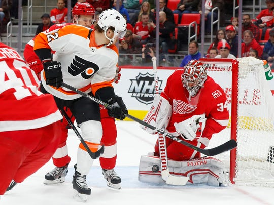 Red Wings goaltender Petr Mrazek (34) stops a Flyers left wing Michael Raffl (12) shot in the first period on Tuesday, Jan. 23, 2018, at Little Caesars Arena.