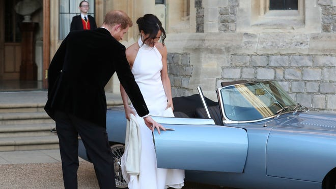Gallant Prince Harry, left, wearing a dinner jacket, opens the car door for his new bride, Meghan Markle, before heading to an evening reception hosted by Harry's father, Prince Charles, after the couple's royal wedding earlier Saturday.