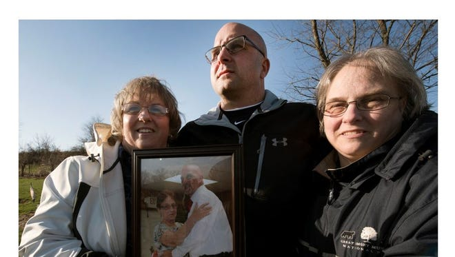 John Barton is joined by his sisters Tammy (Shaffer) Smith, left, and Pam (Shaffer) Cool, on Thursday at the Waynesboro cemetery where their mother and brother are buried. They are holding a photo of their mother, Shirley Shaffer, and brother, Clinton Shaffer Jr.