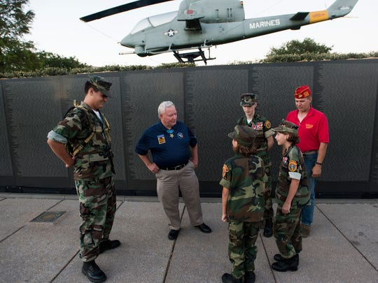 """Medal of Honor recipient Donald """"Doc"""" Ballard, center, talks with a group of Young Marines and Marine Corps League member Cliff Zack, right, after the kickoff of the Heroes Among Us speaker series on Thursday, May 25, 2017, at Veterans Memorial Park in Pensacola."""