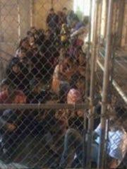 Detainee kids behind chain link fencing